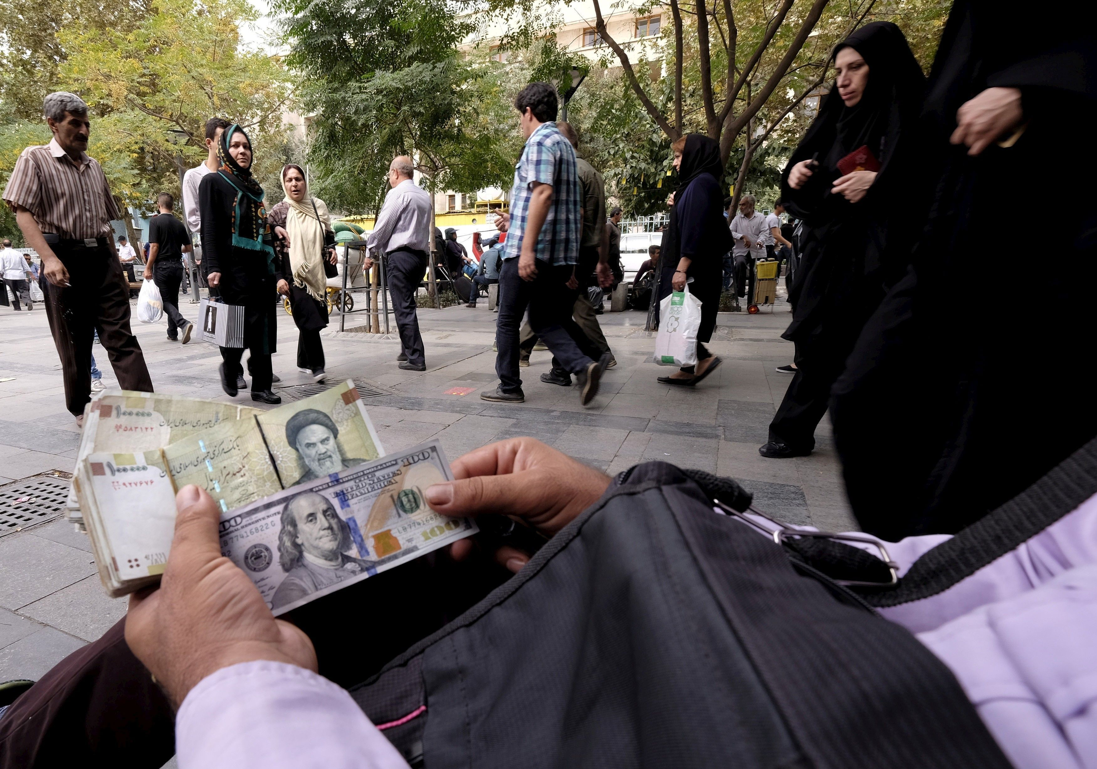 FILE PHOTO: A money changer displays U.S. and Iranian banknotes at the Grand Bazaar in central Tehran. REUTERS./