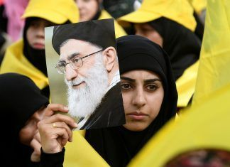 A woman carries a picture of Iran's Supreme Leader Ayatollah Ali Khamenei