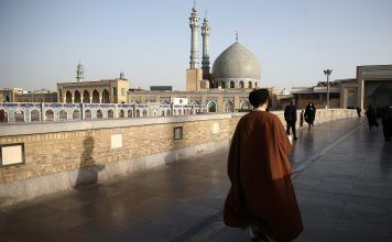 FILE PHOTO: An Iranian cleric walks in front of the Shrine of Fatima Masumeh in Qom, Iran. REUTERS./