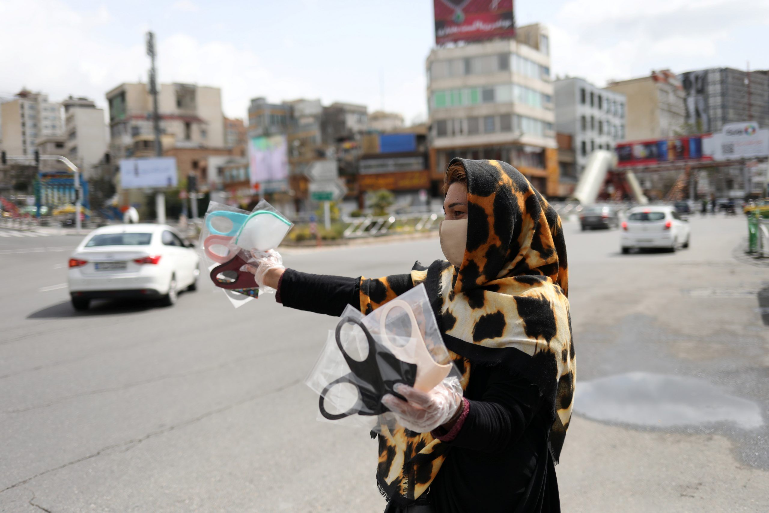 A woman wears a protective face mask and gloves, amid fear of the coronavirus disease (COVID-19), as she sells the masks in Tajrish square in Tehran, Iran.  REUTERS./