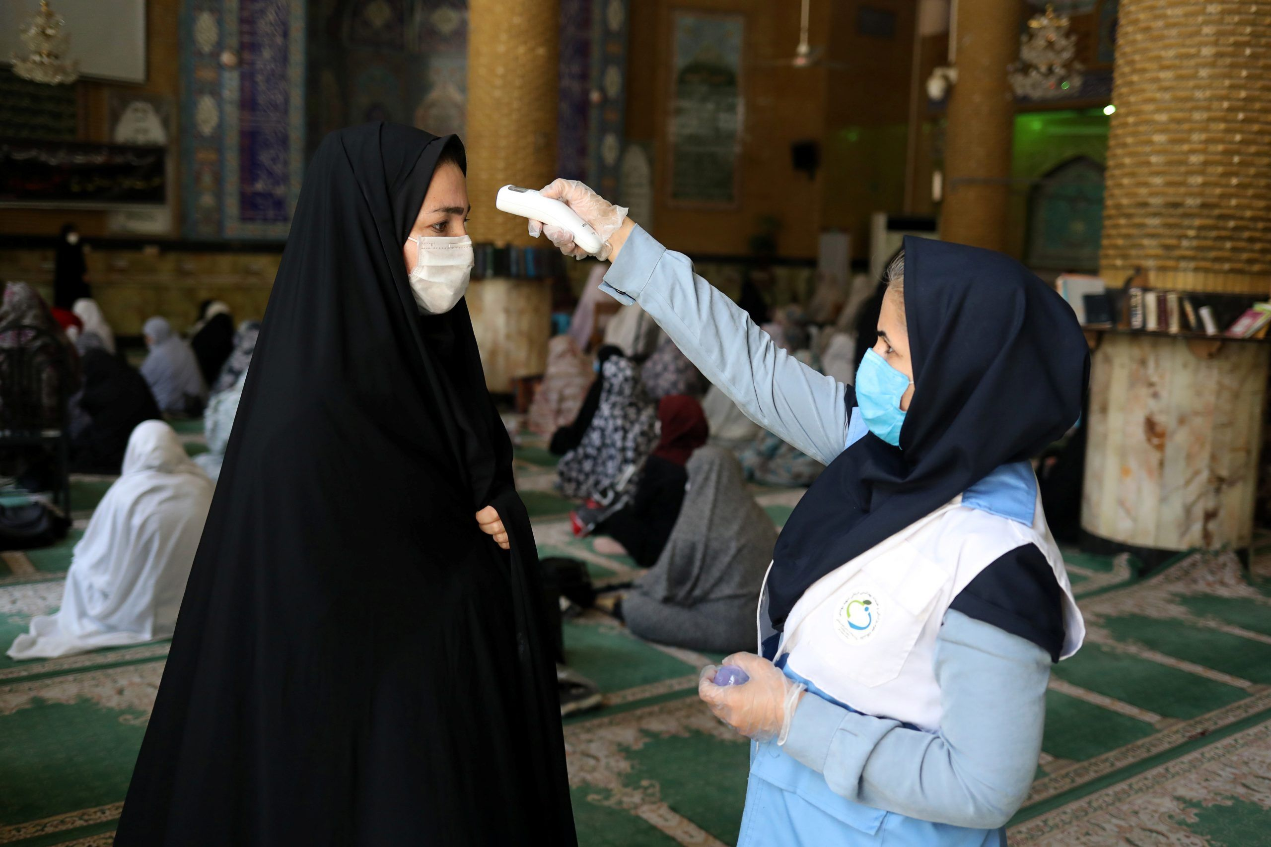 An Iranian woman wearing a protective face mask checks the temperature of a worshipper before attending the Friday prayers in Qarchak Jamee Mosque, following the outbreak of the coronavirus disease (COVID-19), in Tehran province, in Qarchak, Iran, June 12, 2020. REUTERS./