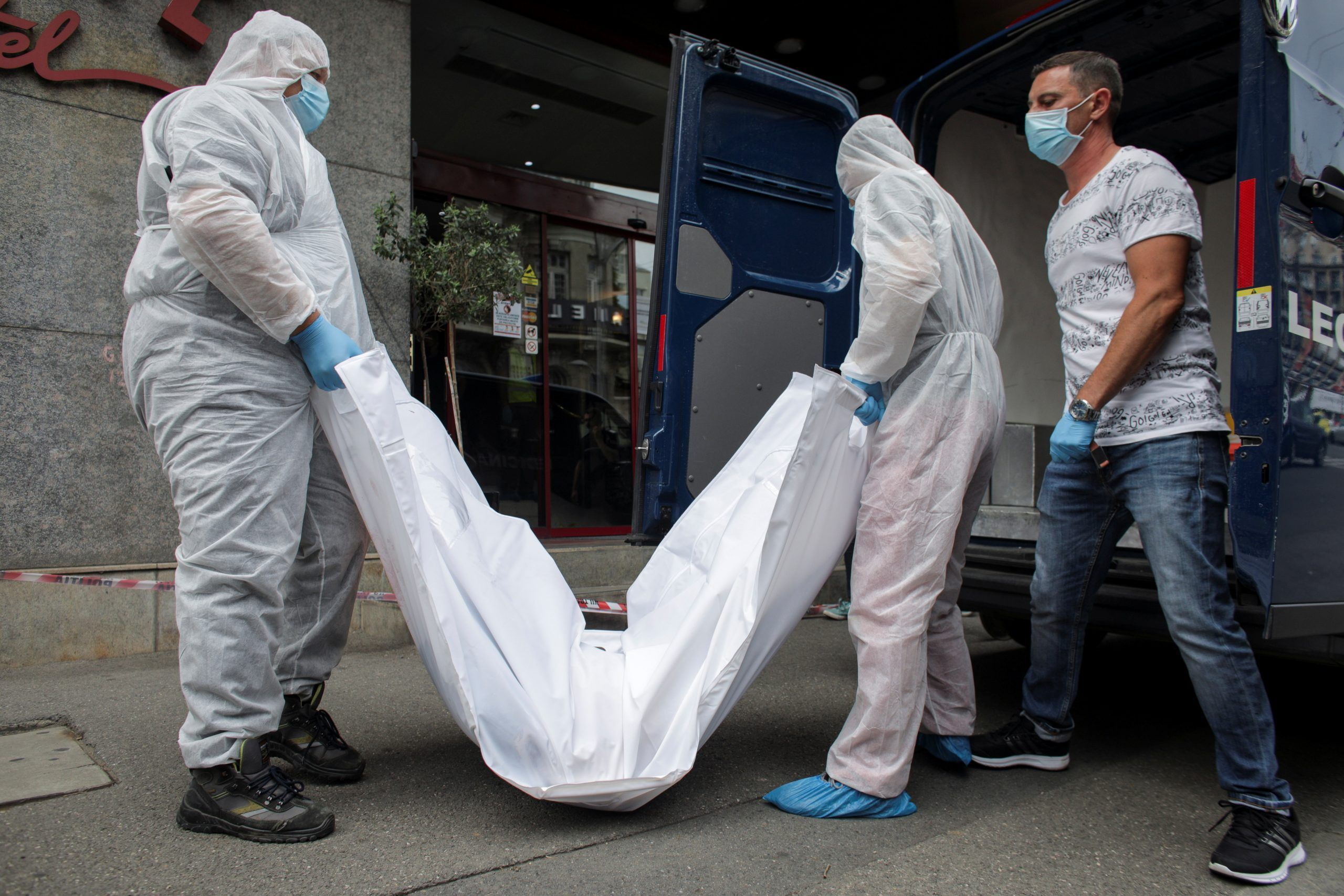 Forensic medicine staff carry a body bag, allegedly containing the remains of Gholamreza Mansouri, outside a hotel in downtown Bucharest, Romania, June 19, 2020.