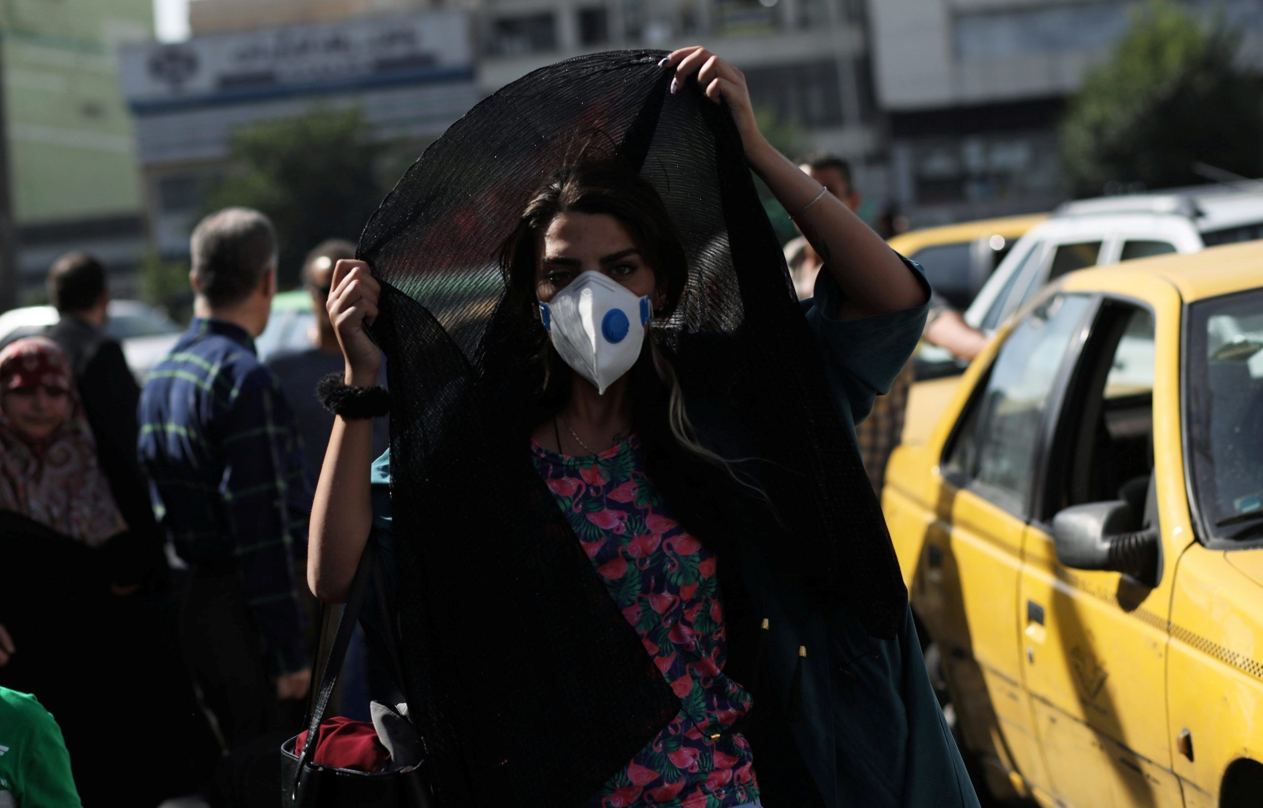 A woman wearing a protective face mask walks in a street, following the outbreak of the coronavirus disease (COVID-19), in Tehran, Iran. REUTERS./